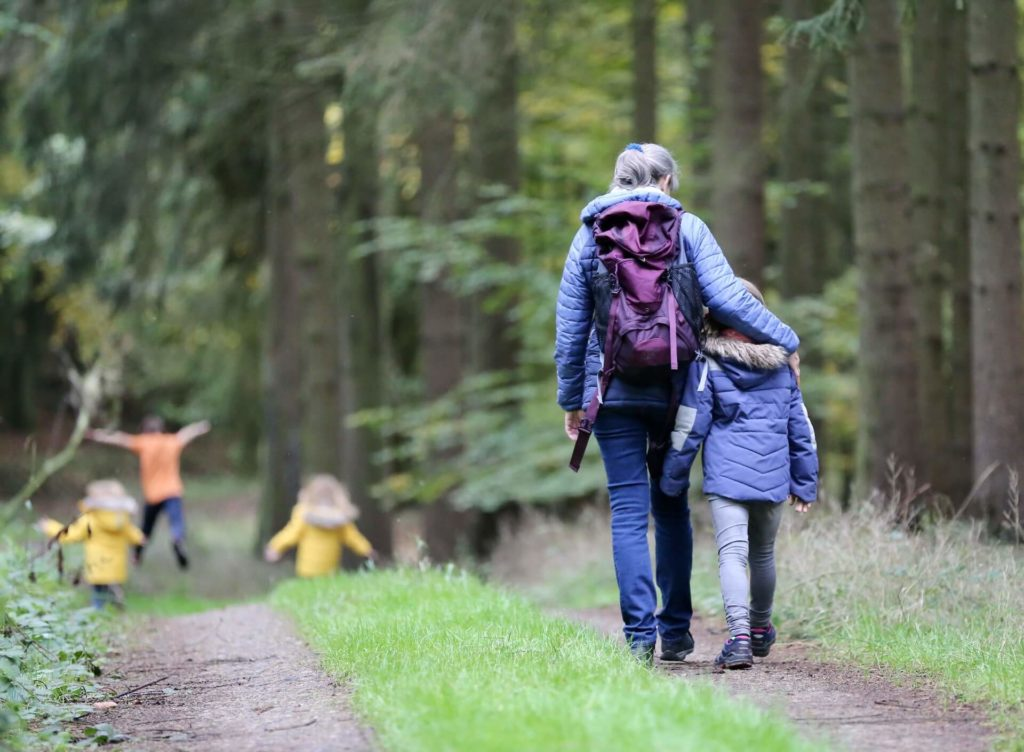 Madre e hija caminando por el bosque con unas chaquetas para el frio